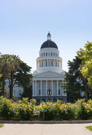 Backlit morning scene of the front of the California State Capitol building in the capital of Sacramento with roses framing the scene Stock Photo