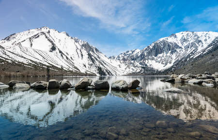 Reflection of snow covered mountains in picturesque Convict Lake in Sierra Nevada California