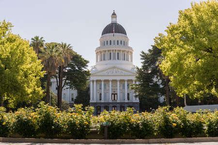 Escena de mañana retroiluminada del frente del edificio del Capitolio del Estado de California en la capital de Sacramento con rosas que enmarcan la escena