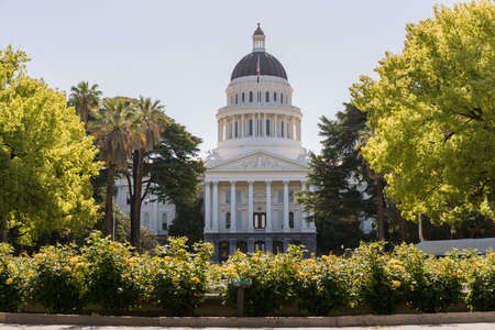 Backlit morning scene of the front of the California State Capitol building in the capital of Sacramento with roses framing the scene Archivio Fotografico