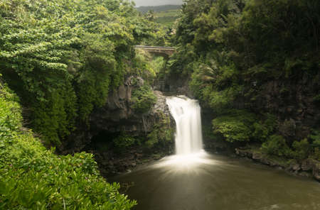 Road to Hana continues over bridge over waterfall into Seven Sacred Pools at state park 写真素材