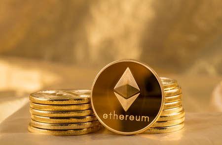 エーテル硬貨または blockchain とサイバー通貨を説明するためにゴールドの背景に ethereum のスタック 写真素材