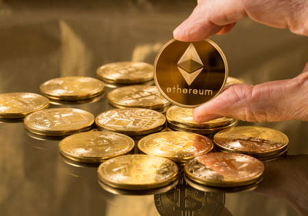 Hand holding a single ether or ethereum coin over bitcoins on gold background to illustrate blockchain and cyber currency Standard-Bild