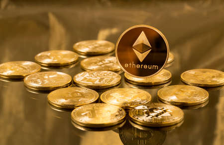 Single ether or ethereum coin over bitcoins on gold background to illustrate blockchain and cyber currency Foto de archivo