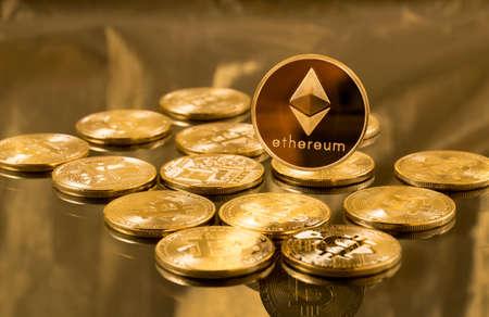 Blockchain とサイバー通貨を説明するためにゴールドの背景に bitcoins を単一エーテルまたは ethereum コイン 写真素材