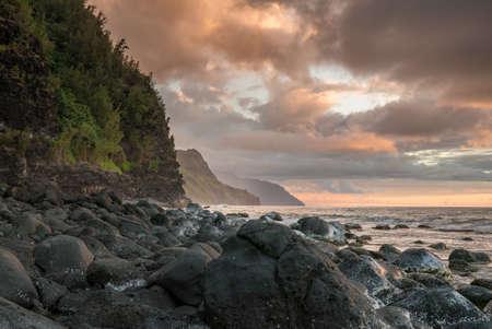 Sun setting over the receding headlands of the Na Pali coast from Kee Beach on north of Kauai, Hawaii