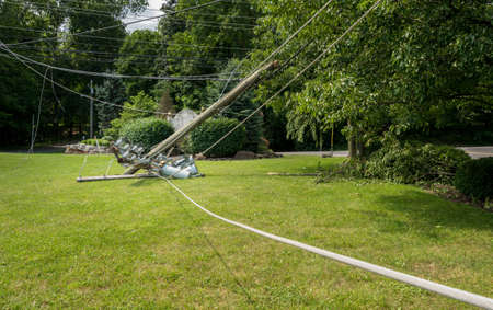 Broken snapped wooden power line post with electrical components on the ground after a storm