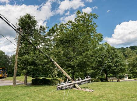Rompió el poste de madera de la línea eléctrica quebrada con los componentes eléctricos en la tierra después de una tormenta