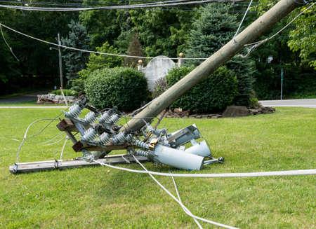 Gebroken gebroken houten krachtlijnpaal met elektrische componenten op de grond na een storm Stockfoto