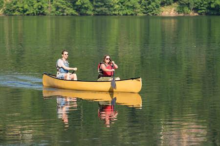 Mannelijke en vrouwelijke Kaukasische paar, die een gele kano op een zeer rustige ochtend op een boomgaarde meer laat roeien
