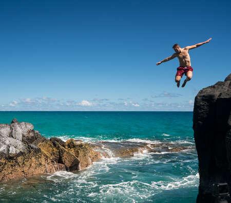 Dangerous leap into warm blue ocean off rocks at Lumahai Beach on Hawaiian island of Kauai