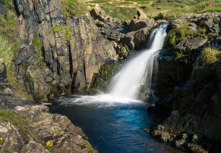 Small waterfall in river falling towards the sea at Welcome Mouth in North Devon Stock Photo
