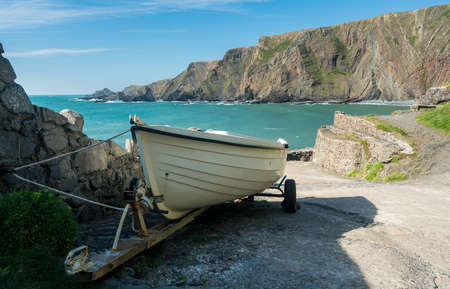 White wooden rowing boat ready to launch at pier at Hartland Quay in North Devon, England Stock Photo