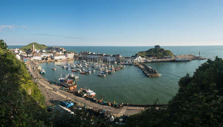 ILFRACOMBE, DEVON UK – JULY 24:  Harbor at sunrise on 24 July 2017 in Ilfracombe, UK. The Damien Hirst statue Verity was erected in 2012 Editorial