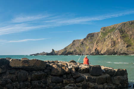Man fishing in the ocean at Hartland Quay in North Devon, England Stock Photo