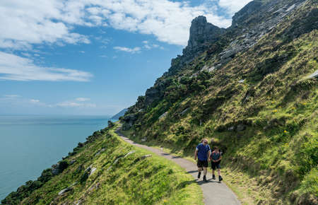 lynton: LYNMOUTH, DEVON UK – JULY 24:  Hikers on the South West Coast Path on 24 July 2017 in Lynmouth, UK. The highest point on this path is 1043 feet above the sea.