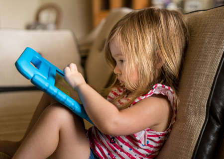Young girl sitting at home on settee and using a childs tablet touch screen computer Stock Photo