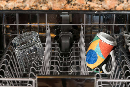 Cup and clear glass remain in dishwasher after a clean and rinse