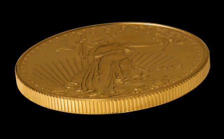 Isolated view of the side of a one ounce gold eagle coin minted in the USA Stock Photo