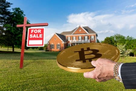 Businessman or finance executive in suit offering bitcoin to purchase large single family home
