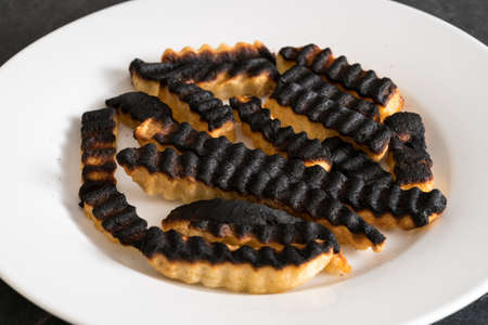 Burnt and ruined french fries or chips after leaving under the grill for too long and charring them