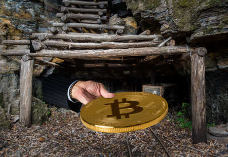 Miner engaged in mining for new bitcoins holds out a coin out of the entrance to an old coal mine Stock Photo