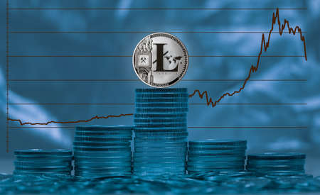Single Litecoin coin on stack of silver coins with graph of price change against US dollar in background Stock Photo