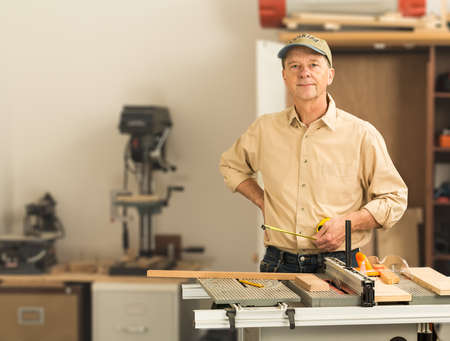 Senior man working on tools in home workshop with table saw, bench drill and other equipment