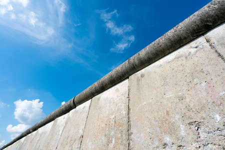 Concrete top of the Berlin Wall in Germany against a bright blue sky Stock Photo