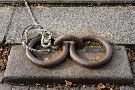 Two old iron rings and knotted rope used to moor a boat off Copenhagen canal