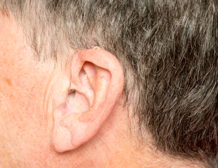 Macro close up of tiny modern hearing aid placed behind the ear of senior adult man Stock Photo