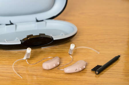 Macro close up of a matched pair of tiny modern hearing aids with case and brush on wooden bedside dressing table