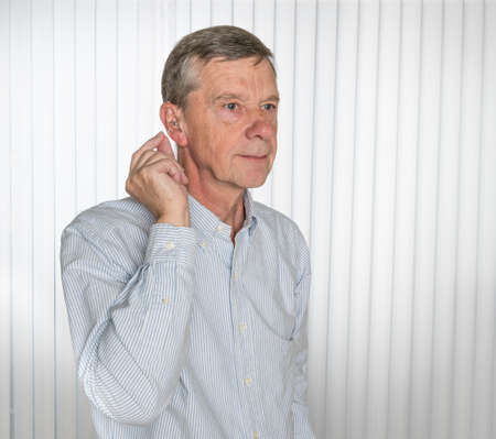 Senior caucasian man holding a tiny modern hearing aid before inserting in his ear