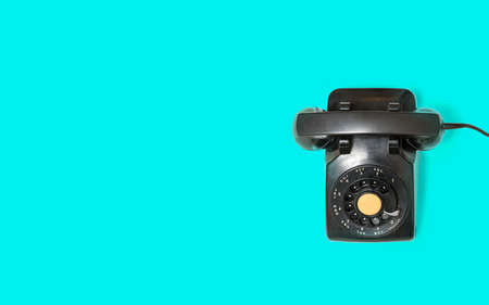 Aerial view of old and antique rotary telephone on turquoise background Banco de Imagens