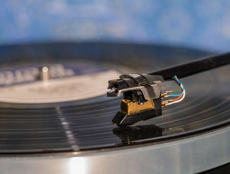 Side view of a playing vinyl record on vintage hi-fi stereo turntable with tonearm and cartridge in tracks of the LP Stock Photo