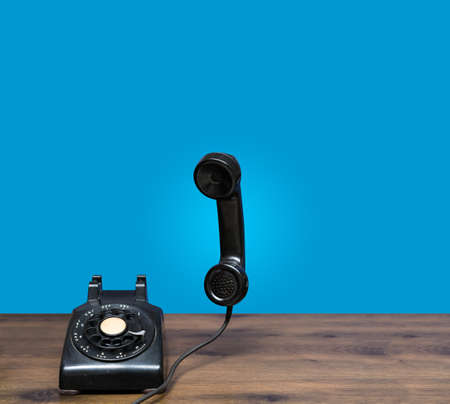 Antique rotary telephone on wooden desk with handset floating in the air ready for answering call Stock Photo