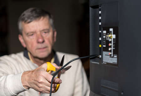 Close up of senior caucasian retired man cutting the aerial connection to his TV to illustrate cutting the cord