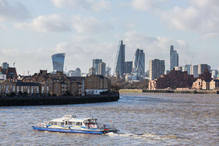 런던, 영국 -1 월 30 일 : 2020 년 1 월 30 일 : Thames 클리퍼와 런던 시티에있는 주요 사무실 건물의 스카이 라인 Doubletree Hotel에서 페리 보트를 타고 Canary Whar 에디토리얼