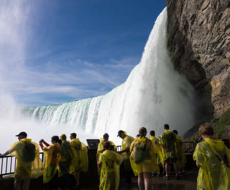 NIAGARA FALLS, CANADA - JUNE 30, 2016: Tourists at the Journey behind the Falls by the Canadian or Horseshoe waterfall  of Niagara Falls 写真素材 - 90561662
