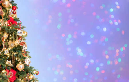 Ornately decorated christmas tree with defocused lights on blue background for copy space for holiday message