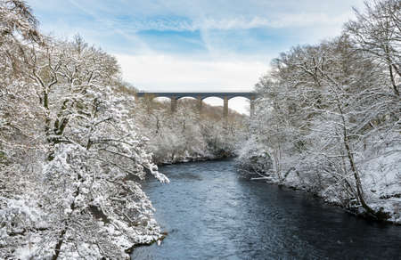 Snow covered trees frame the old Pontcysyllte Aqueduct near Chirk carrying Llangollen Canal across river Dee 스톡 콘텐츠