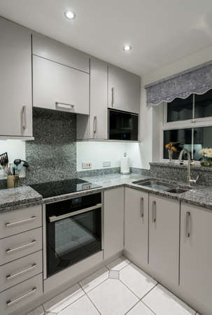 Small Modern Kitchen In UK Apartment With Granite And New Appliances  Including Induction Cooktop Stock Photo