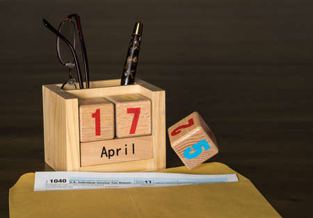 Wooden letters in calendar with Form 1040 income tax for 2017 showing tax day for filing is April 17 2018 Stock Photo