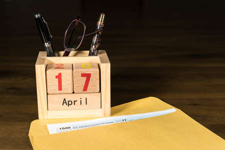 Wooden letters in calendar with Form 1040 income tax for 2017 showing tax day for filing is April 17 2018 写真素材