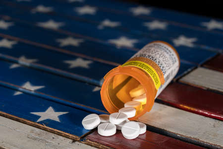 Oxycodone is the generic name for a range of opoid pain killing tablets. Prescription bottle for Oxycodone tablets and pills on wooden  USA flag