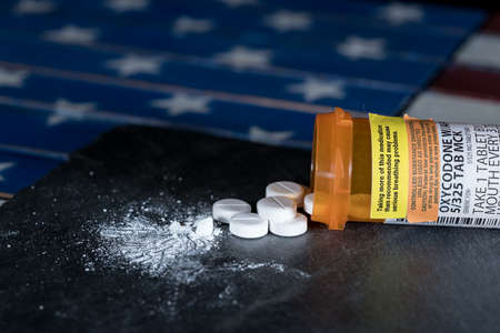Oxycodone is the generic name for a range of opoid pain killing tablets. Prescription bottle for Oxycodone tablets and pills on slate table with USA flag in background