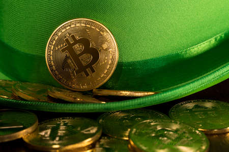 Treasure of golden bitcoins inside a green velvet hat on wooden table to celebrate luck on St Patricks Day of March 17th