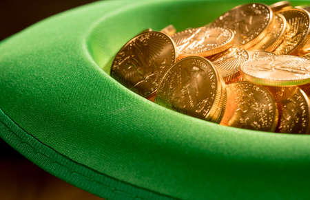 Treasure of pure gold eagle coins inside the rim of a green velvet hat to celebrate luck on St Patricks Day of March 17th Stock Photo