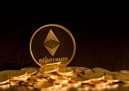 Stack of ether coins or ethereum on gold background to illustrate blockchain and cyber currency