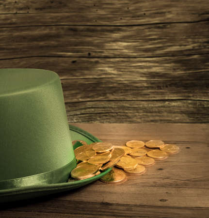 Treasure of pure gold coins inside the rim of a green velvet hat. Placed on wooden table to celebrate luck on St Patricks Day on March 17th